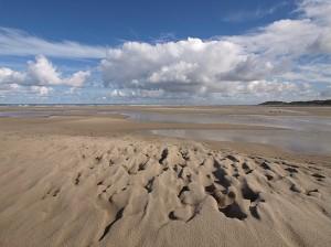 strand met zandstructuur en wolkenlucht
